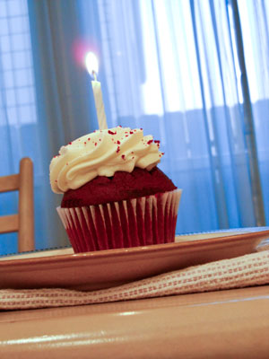 A cupcake with a burning birthday candle