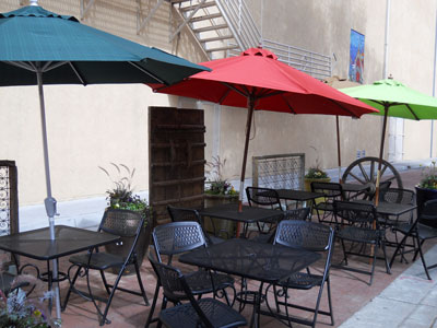 Black iron tables and chairs, shaded with umbrellas, line Burro Alley in Santa Fe
