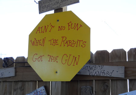 "A sign that says ""Ain't No Fun When The Rabbits Got The Gun"""
